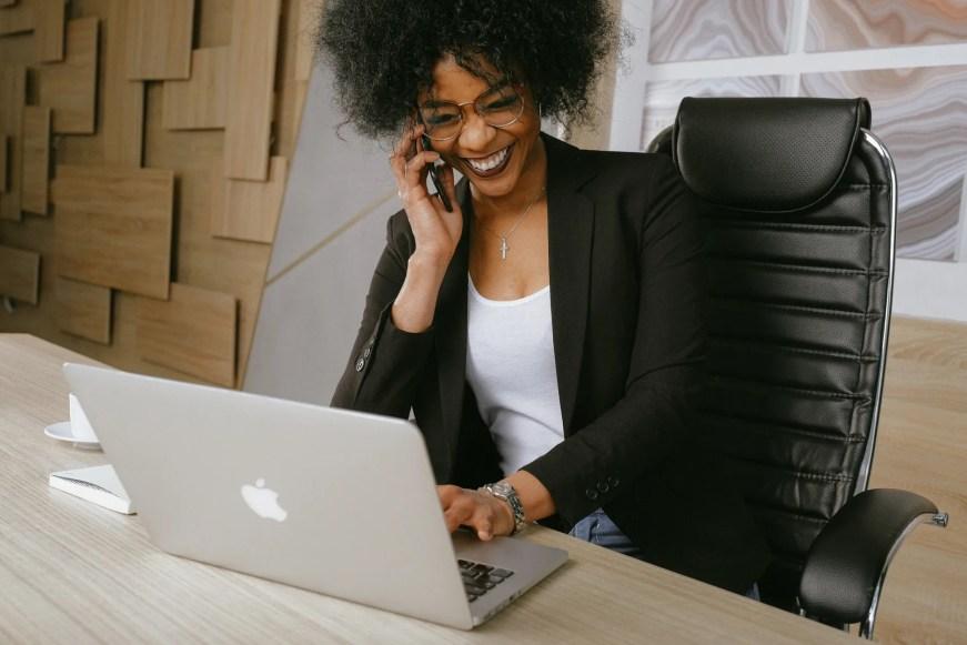 Mulher falando ao telefone no trabalho sorrindo.