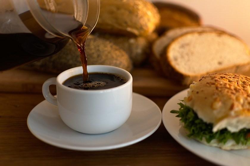 Café sendo colocado na xícara com vários pães ao redor.