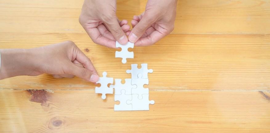 Mãos adicionando duas peças em um quebra-cabeça.