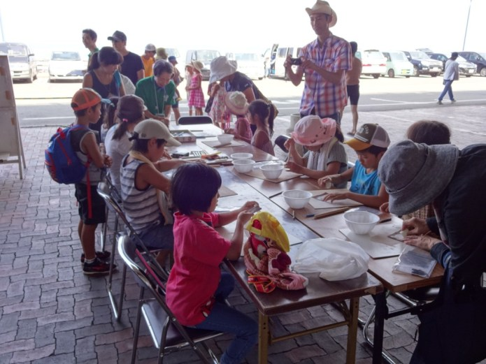 Children and adults try their hand at making magatama beads