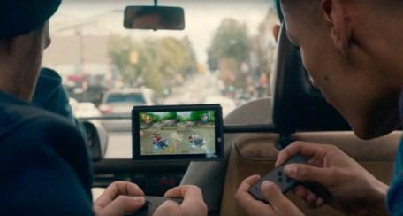 Cette image représente deux joueurs en voiture, en plein gaming avec la Switch.