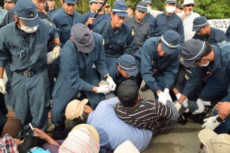 座り込む市民を排除しようとする機動隊員=18日午前9時20分、東村高江の北部訓練場N1地区ゲート前