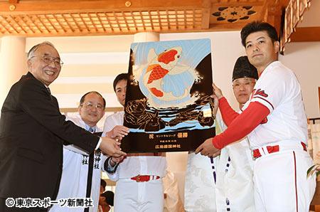 神社から贈られた鯉の盾を披露する松田元オーナー(左)と緒方監督