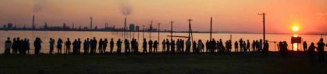 夕日が沈むシャッターチャンスを狙い、大勢の人が海岸に集まった=木更津市の江川海岸