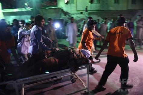 パキスタン・バルチスタン州のシャー・ヌーラー二霊廟で発生した爆発事件の負傷者をカラチの病院に搬送する救急隊員ら(2016年11月12日撮影)。(c)AFP/RIZWAN TABASSUM
