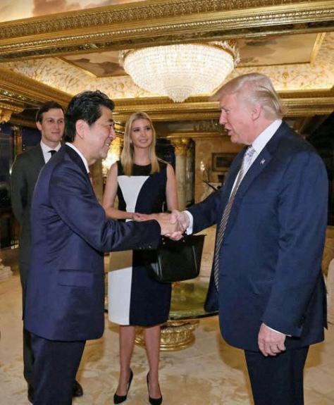 握手を交わす安倍首相(左)とトランプ次期米大統領。後方右はイヴァンカ氏、同左はイヴァンカ氏の夫クシュナー氏(内閣広報室提供・ロイター)