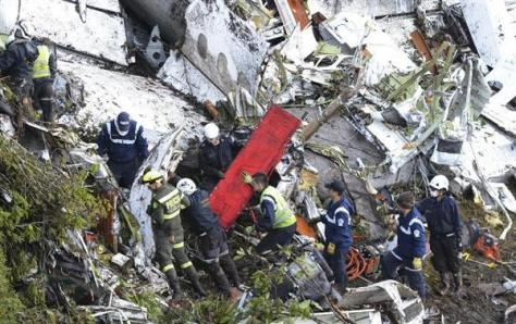 29日、コロンビア・メデジン近郊のチャーター機墜落現場で救助活動する人たち(AP)