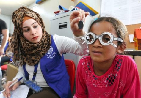 避難民キャンプで、眼鏡をつくるため視力検査をする少女=イラク北部アルビル近郊、杉本康弘撮影