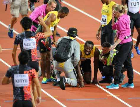 男子400メートルリレー決勝で、負傷するボルト。左は銅メダルを喜ぶ藤光と桐生