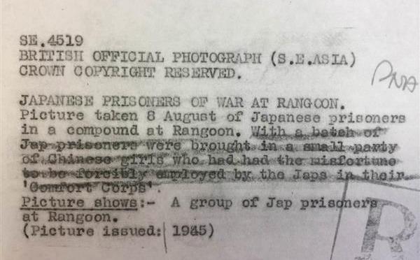 1945年8月8日にビルマ(ミャンマー)のラングーンの日本軍捕虜収容所で英兵士に撮影された日本軍兵士のキャプション。「中国人少女たちを強制的に慰安婦にしていた」と記されながら、不可解にも横線で消されている(英帝国戦争博物館所蔵、岡部伸撮影)