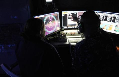 輸送揚陸艦ポンスの艦内で、レーザー兵器システム「LaWS」の操作システムの画面を確認する乗員(米海軍提供)