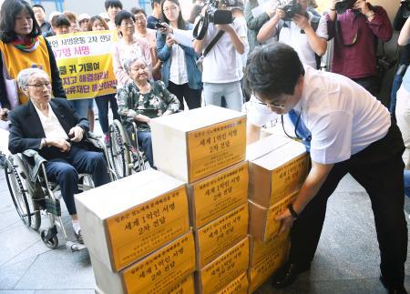 元慰安婦の女性(車いすの2人)らが持ち込んだ署名を運ぶ日本大使館職員(右)=13日、ソウル(共同)