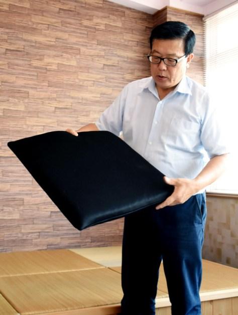 将棋のプロ対局で活躍する座布団を手に取るシーエンジの高岡伸行社長=愛知県蒲郡市
