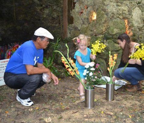 荒らされたチビチリガマに花を手向ける親子(右側)=16日、沖縄県読谷村波平のチビチリガマ