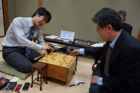終局後、笑みを浮かべながら、脇謙二八段(右)と感想戦を行った藤井聡太四段