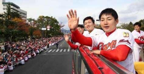 オープンバスで手を振り沿道の声援に応える丸選手(手前)たち=25日午前10時49分、広島市中区(撮影・井上貴博)
