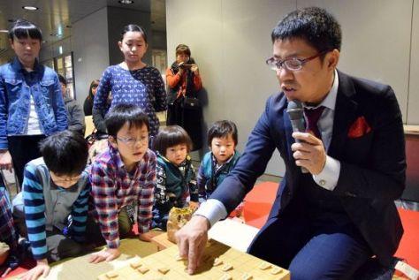 子どもたちに駒の並べ方を教える野月浩貴八段(右)