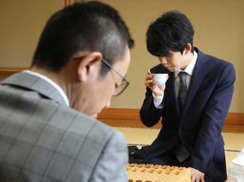 王座戦決勝トーナメント1回戦で屋敷九段(手前)と対戦する藤井六段。屋敷九段の初手を見てお茶を飲む