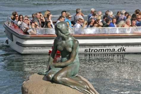 北欧デンマークの首都コペンハーゲンで、人魚姫の像を眺めて夏の一日を楽しむ観光客=2017年8月(共同)