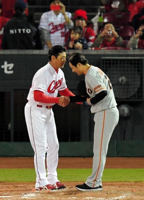 試合後、握手を交わす緒方監督(左)と高橋監督