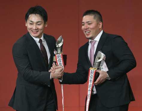 MVPを受賞し、笑顔で握手を交わす広島・丸(左)と西武・山川=27日、東京都内のホテル