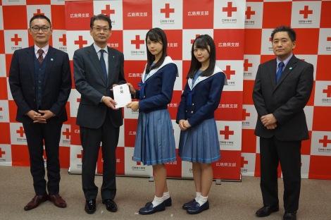 「平成30年7月豪雨災害義援金」の目録を手渡すSTU48の瀧野由美子(中央)と土路生優里