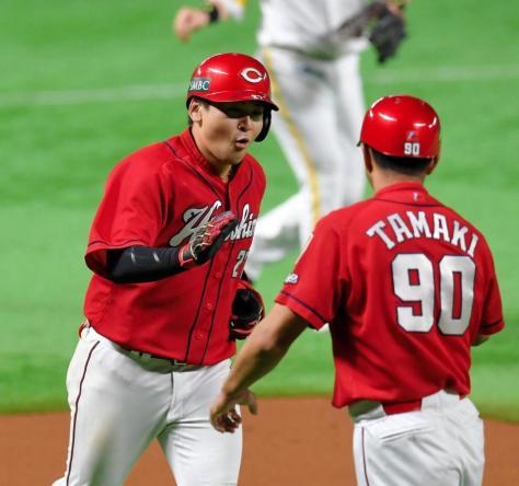 6回、勝ち越しのソロを放ち、驚きの表情で玉木コーチ(右)とタッチを交わす会沢