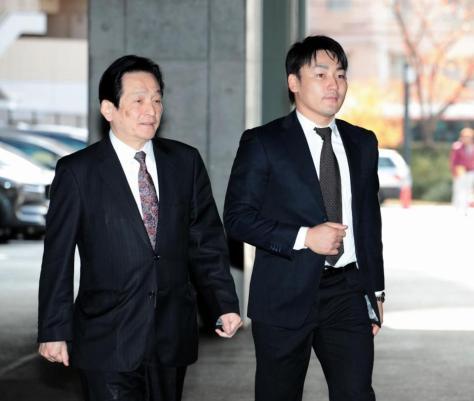 オーナーへの報告を終え、鈴木球団本部長(左)と会見に向かう丸(撮影・坂部計介)
