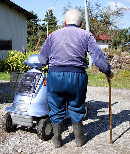 愛用の電動車いすに手を掛ける男性。歩行にはつえを使用しているが、キノコ採りはやめられなかった=川西町