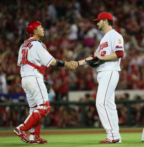 1安打完封勝利を挙げ、石原(左)とがっちり握手を交わすジョンソン(撮影・栗木一考)