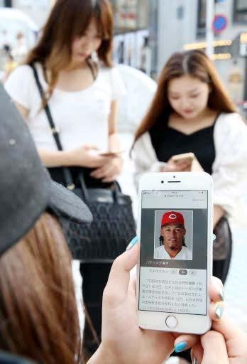 バティスタ選手の処分のニュースをスマートフォンで確かめる女性たち=広島市中区(撮影・河合佑樹)