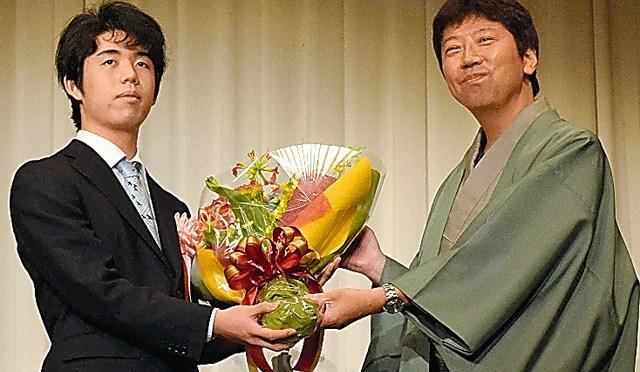 藤井聡太七段(左)から花束を受け取って笑顔の杉本昌隆八段=2019年6月9日、名古屋市
