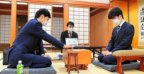 藤井聡太二冠(右)と対戦し、初手を指す谷川浩司九段=9月9日、大阪市福島区