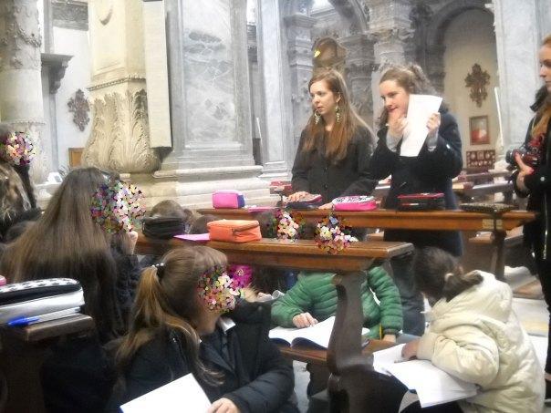 I bambini seduti fra i banchi di preghiera della chiesa di Santa Maria dei Miracoli