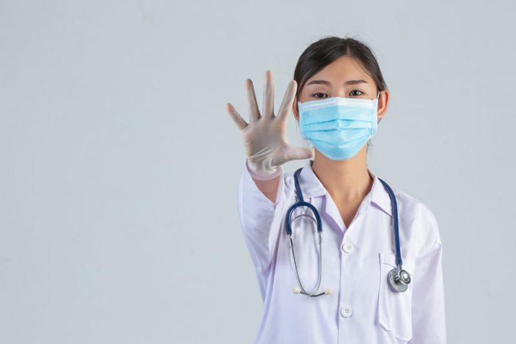 Medico con mascherina e guanti fa segno di fermarsi
