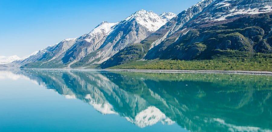 Mountains reflecting in still water of Glacier Bay. Glacier Bay National Park and Preserve, Alaska, United States