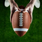 American football player holds ball