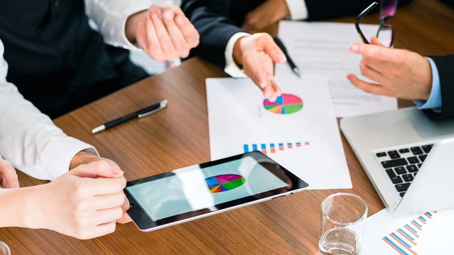 Finance and business partners collaborate over report data