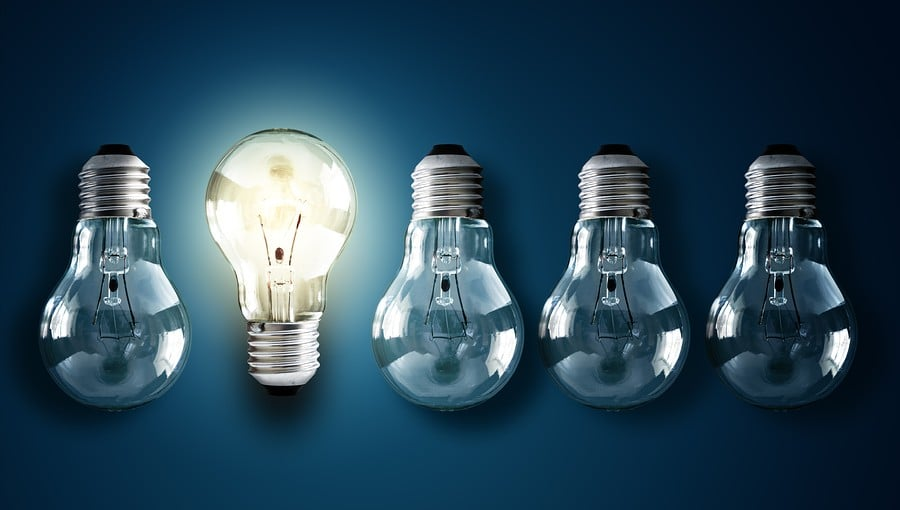 Light bulb illuminated in row of dim ones