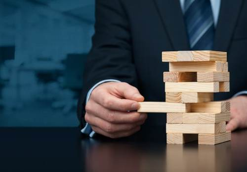 Metaphor of risk in business. Risk management concept. Businessman remove one piece from tower wide banner