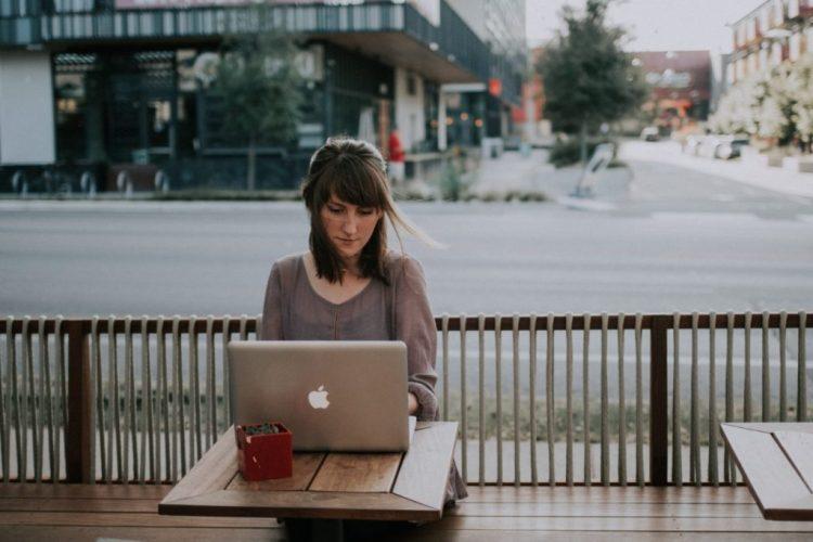 Mulher trabalhando em seu notebook, sentada em uma mesa de uma cafeteria ao ar livre. Imagem representa a liberdade de trabalhar onde quiser com um escritório virtual
