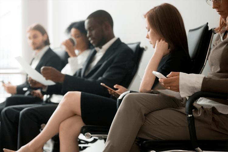 Vários advogados e advogadas sentados em uma fileira de cadeiras em uma espécie de sala de espera, todos manuseando smartphones. A foto representa a conectividade online do advogado e a importância de um blog de advogados.