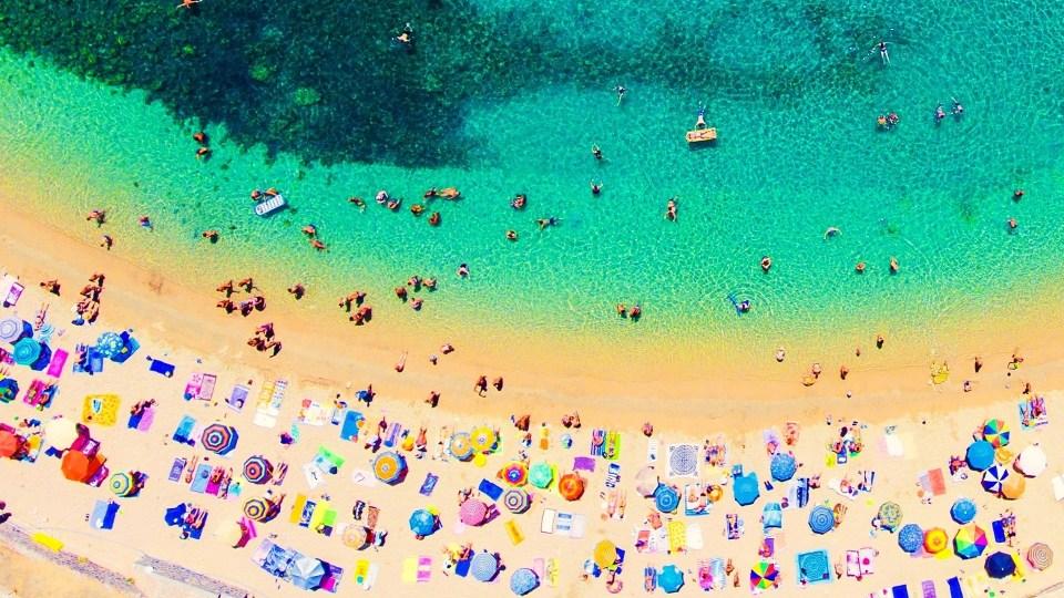 piaszczysta plaża zlotu ptaka zkolorowymi parasolami oblana turkusową wodą, wktórejpływają ludzie   kiedy najlepiej jechać doGrecji