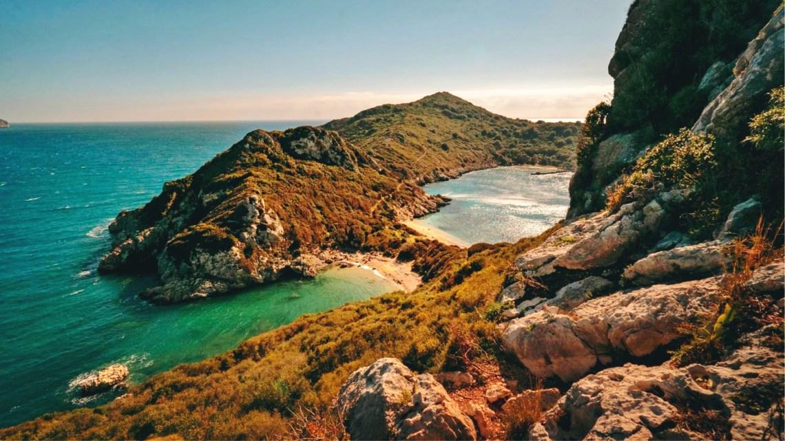 brązowe wzgórza porośnięte roślinnością rozdzielone dwiema plażami oblanymi lazurowymi wodami na tle błękitnego nieba