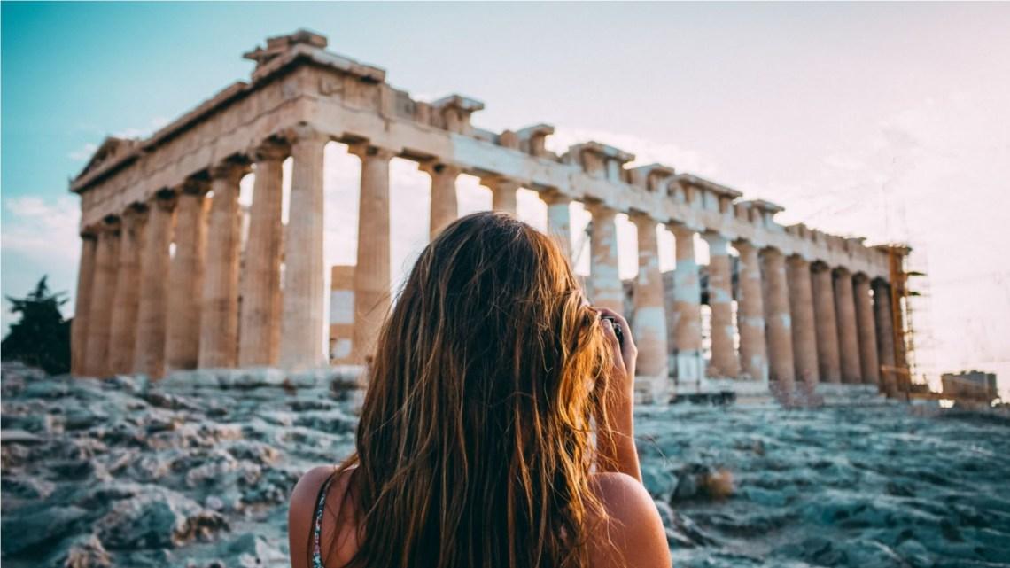 kobieta stojąca naprzeciwko Partenonu w Atenach. Grecja poza sezonem
