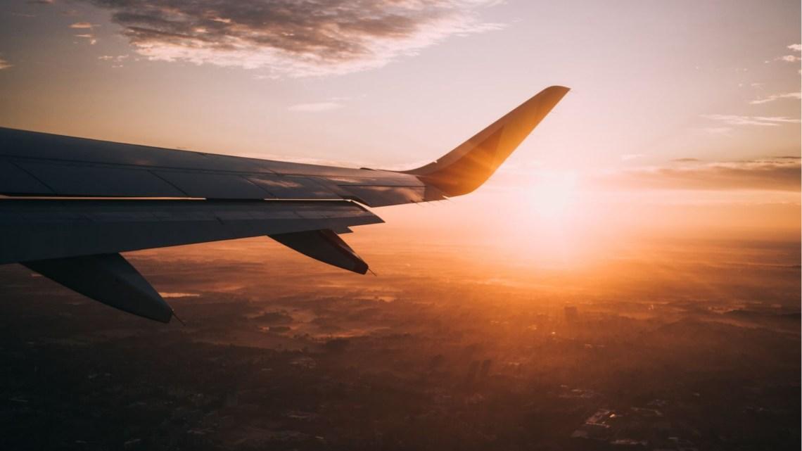 widok na prawe skrzydło samolotu na tle różowego nieba i chmury, w dole zabudowania