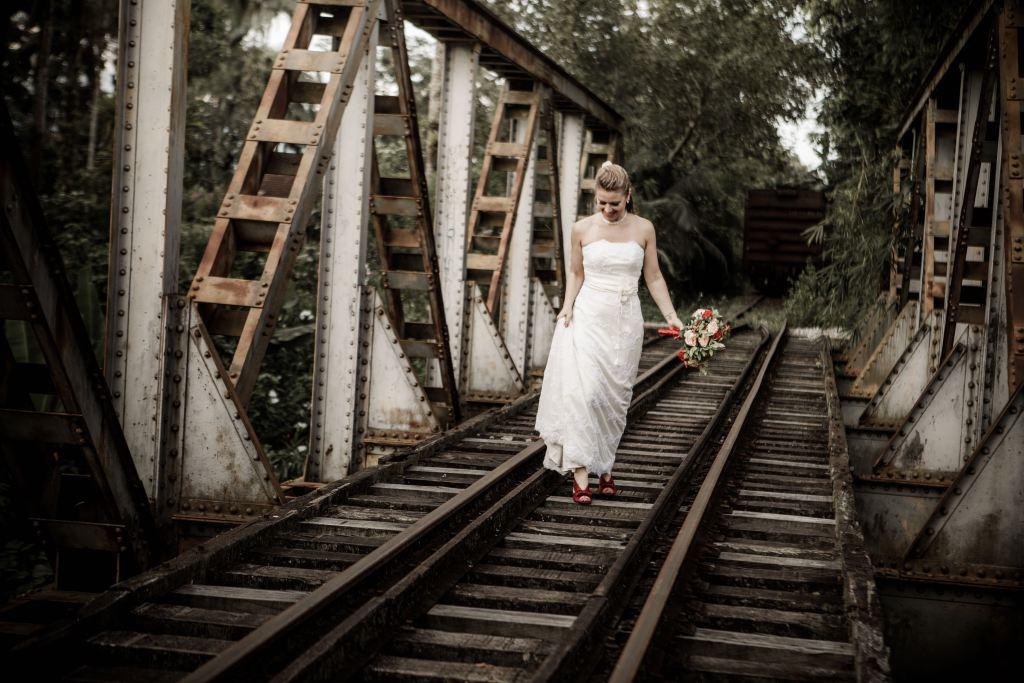Noiva caminhando na trilha do trem. Fotografia no estilo Trash-The-Dress, durante o dia.