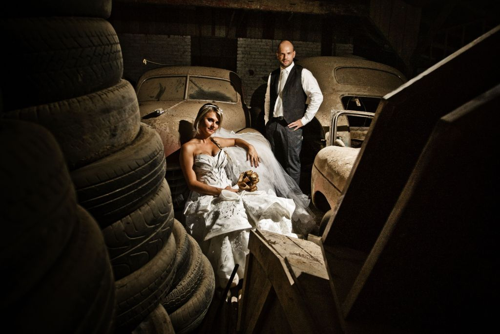 Cena de fotografia de casal em galpão com carros antigos e sujos. Estilo Trash-The-Dress, com noivos em traje de casamento.