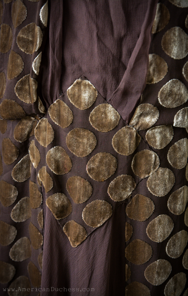 Detail of applique work on an antique 1920s tabard style gown in cut velvet and silk chiffon