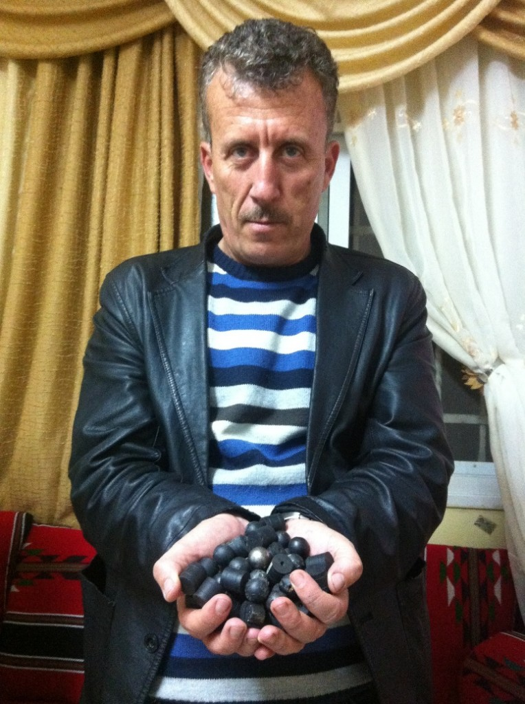 Former prisoner of conscience Bassem Tamimi holds plastic and rubber-coated bullets fired by Israeli forces.
